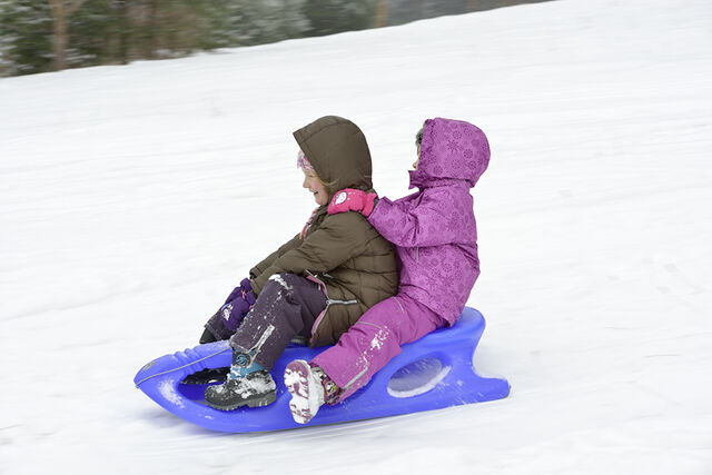 Two children sledding in snow